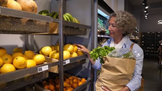 Senior woman shopping at an organic food market looking at the prices of the food on the shelves and choosing the fruits video