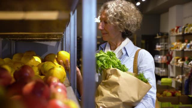 vídeos y material grabado en eventos de stock de mujer senior de compras de frutas y verduras, elegir de una estantería mirando sonriente y feliz - shopping bags
