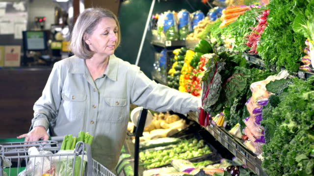 Senior woman shopping for groceries in produce section