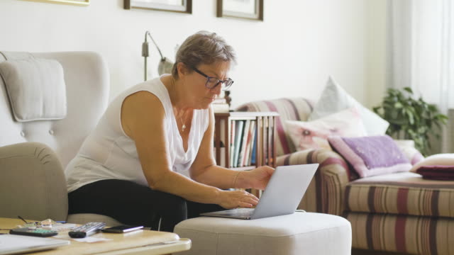シニア女性はクレジットカードでオンラインショッピング - disruptagingcollection点の映像素材/bロール