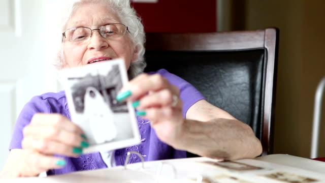 Senior Woman Showing Her Wedding Photo An 89 year old woman looking at then showing a picture of herself in her wedding gown from 65 years ago. the past stock videos & royalty-free footage