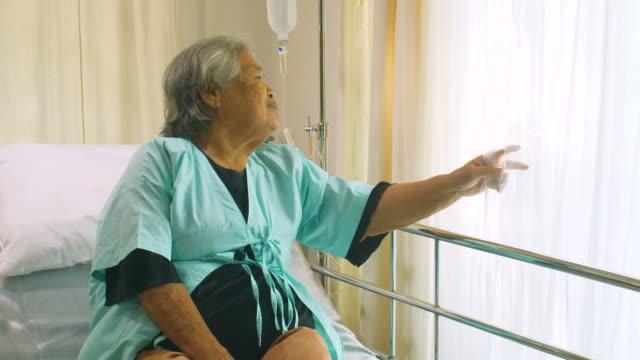 Senior mujer sentado y acostado en la cama paciente en hospital, triste desactivado en cama paciente sentirse solitario. Mujer jubilada solo en una clínica médica. - vídeo