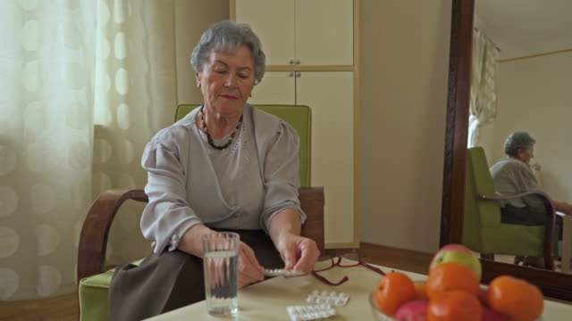 Senior woman sitting at home and taking a pill with a glass of water. video