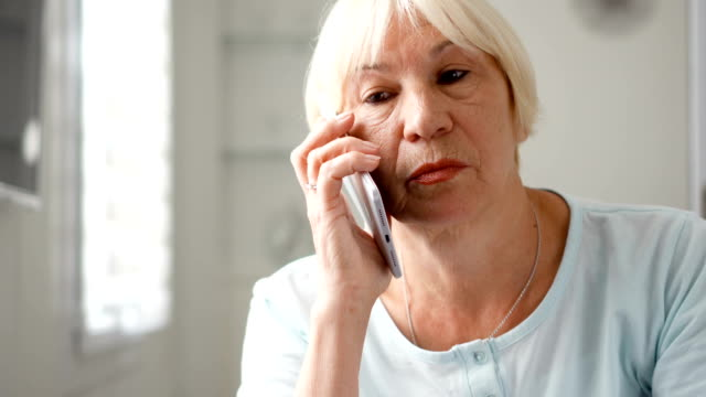 Senior woman sitting at home using smartphone. Retired woman talking on cellphone Good-looking blond senior woman sitting at home using smartphone. Retired woman talking on cellphone. Active modern elderly people concept dial stock videos & royalty-free footage