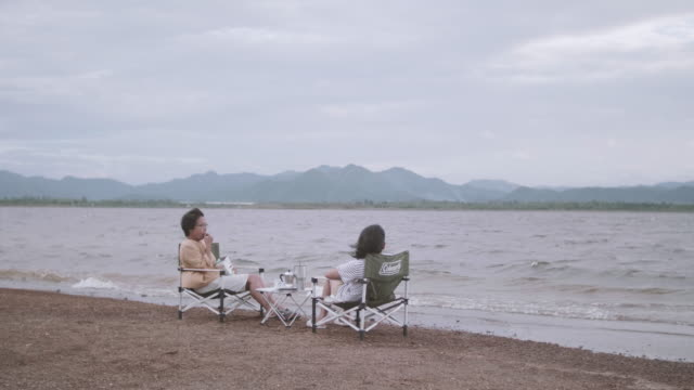 vídeos y material grabado en eventos de stock de senior mujer sentada en su silla de campo escuchando a una mujer más joven hablando. - memorial day