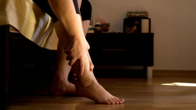 vídeos de stock, filmes e b-roll de senior mulher sentada na cama, fazendo auto massagem de pernas no quarto dela - perna termo anatômico