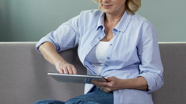 Senior woman sitting on couch and scrolling screen of tablet, reading e-book video