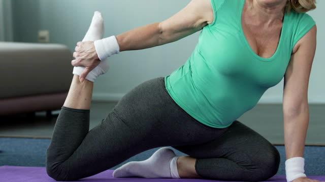 Senior woman sitting on fitness mat, stretching her leg, yoga pose, flexibility video