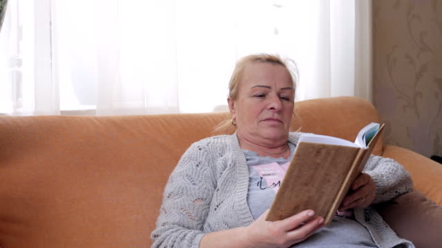 Senior woman sitting on sofa and reading a book video