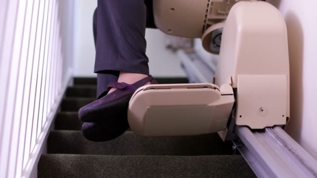 vídeos de stock e filmes b-roll de senior woman sitting on stair lift at home to help mobility - chair