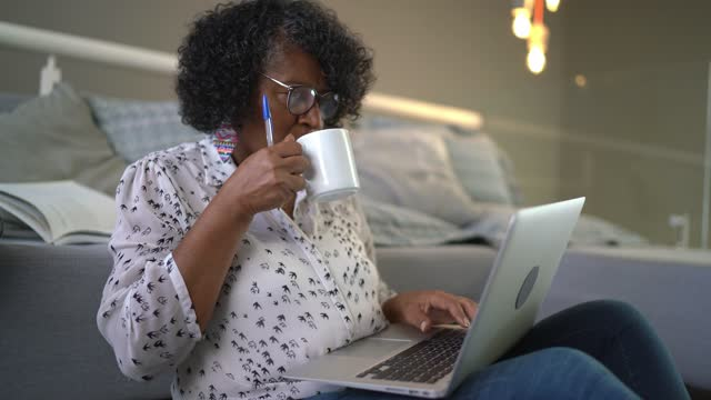 Senior woman sitting on the floor working on laptop at home video