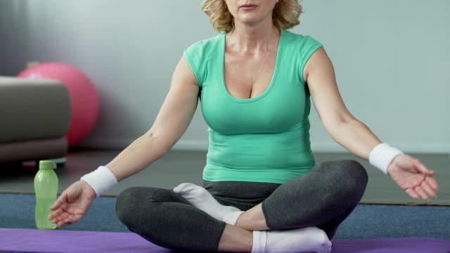 ロータス ポーズ、アクティブなライフ スタイル、瞑想のヨガのマットの上に座っている年配の女性 - 女性選手点の映像素材/bロール
