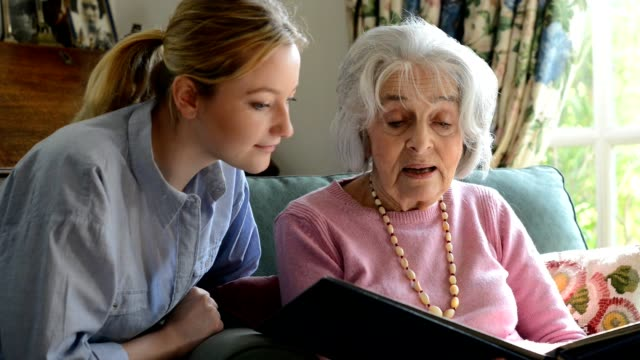 Senior woman sitting with adult granddaughter at home looking through photo album together video