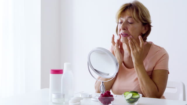 Bидео Senior woman skin care at home