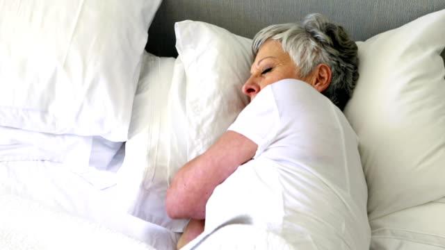 Senior woman sleeping on bed in bedroom video