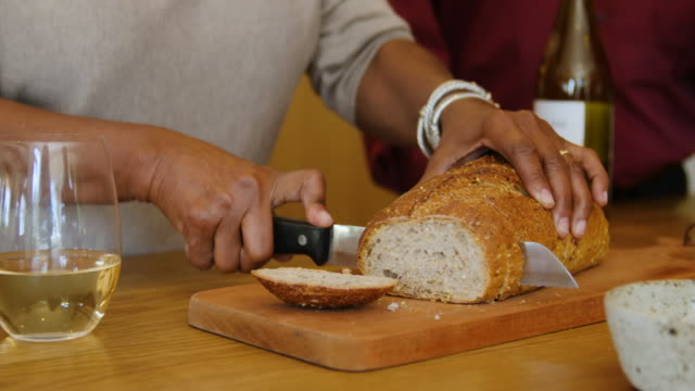 Senior woman slicing bread on cutting board at home