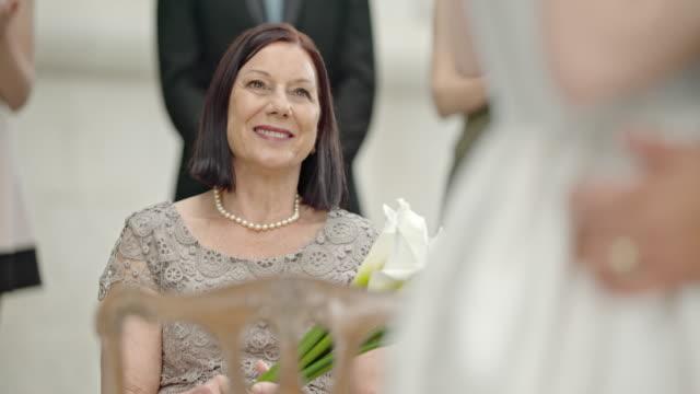 SLO MO Senior woman smiling and applauding at wedding video