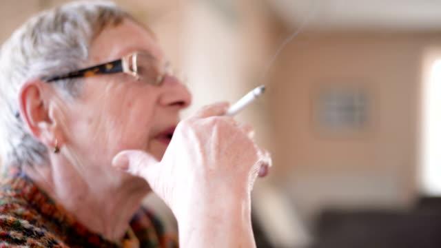 senior donna fumare sigaretta - sigaretta video stock e b–roll