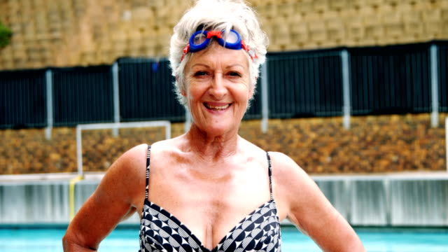 Senior woman standing with hands on hip near poolside video