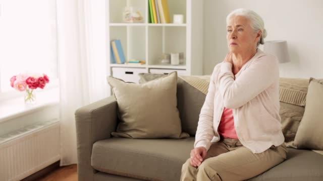 senior kvinna lider av nacksmärta hemma - axel led bildbanksvideor och videomaterial från bakom kulisserna