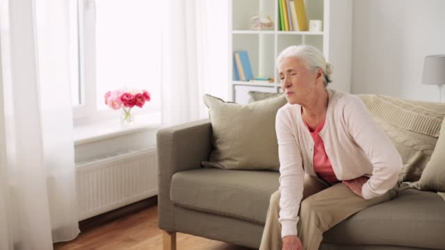 senior woman suffering from pain in leg at home old age, health problem and people concept - senior woman suffering from pain in leg at home knee stock videos & royalty-free footage