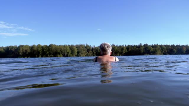湖で泳ぐシニア女性 - disruptagingcollection点の映像素材/bロール