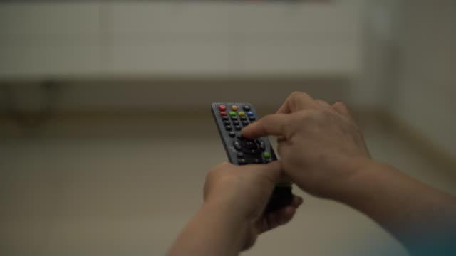 自宅でシニア女性スイッチチャンネルテレビ、4k - 寂しさ点の映像素材/bロール