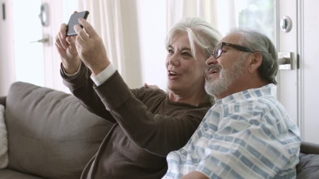 senior woman taking selfie with husband at home - 60 69 anni video stock e b–roll