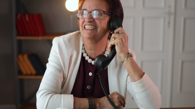 Senior woman talking on telephone at home. Senior woman talking on telephone at home. landline phone stock videos & royalty-free footage