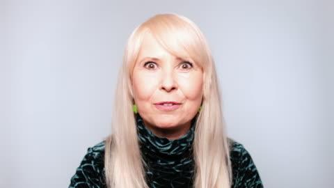 stockvideo's en b-roll-footage met senior vrouw praten op witte achtergrond - gewone snelheid