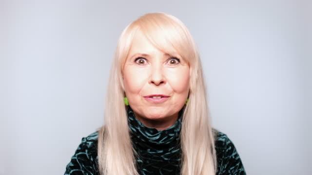 senior kvinna pratar på vit bakgrund - realtid bildbanksvideor och videomaterial från bakom kulisserna