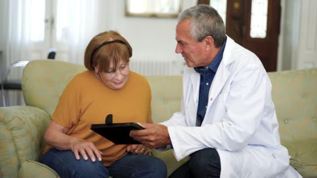 vídeos y material grabado en eventos de stock de mujer mayor hablando con el médico en el hogar de ancianos - geriatría