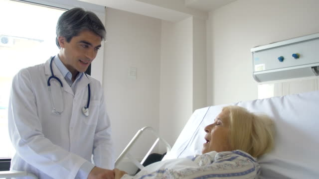 Senior woman talking to doctor while lying on bed video