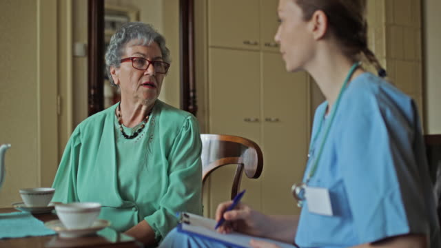 Senior woman talking to home caregiver and drinking tea at home. video