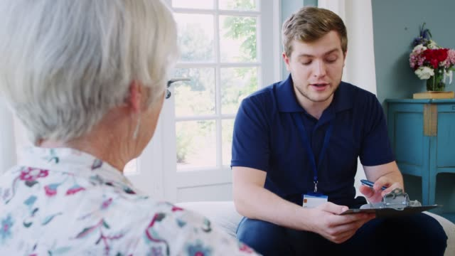 Senior woman talking with male care worker on home visit Senior woman talking with male care worker on home visit sociology stock videos & royalty-free footage