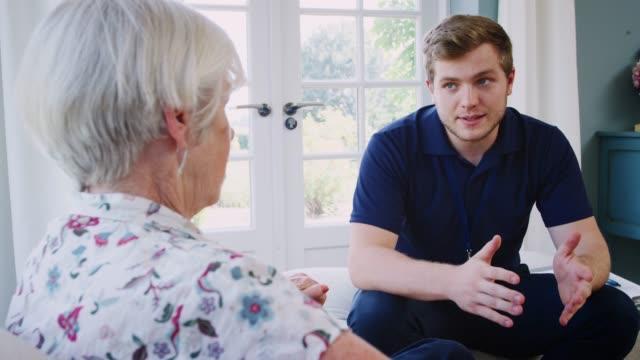 vídeos y material grabado en eventos de stock de senior mujer hablando con trabajadores de cuidado masculino en visita domiciliaria - servicios sociales