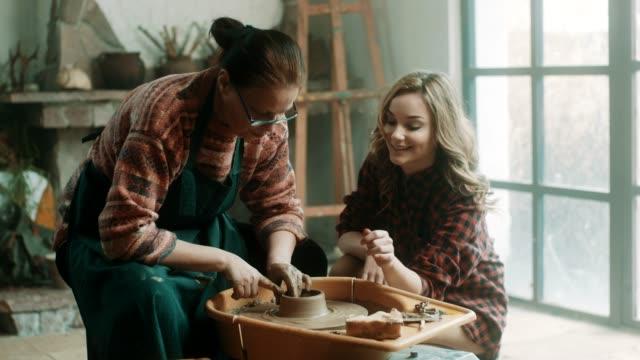 senior woman teaching young woman how to use pottery wheel - sztuka i rzemiosło wytworzony przedmiot filmów i materiałów b-roll