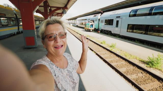 en senior kvinna som reser med tåg tar en selfie - waiting for a train sweden bildbanksvideor och videomaterial från bakom kulisserna