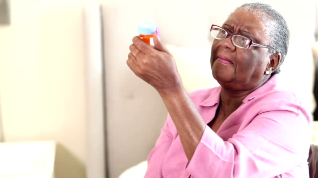 Senior woman trying to read prescription medicine bottle A senior African-American woman having trouble reading the instructions for taking her medication. She is wearing eyeglasses, holding and examining the prescription bottle. pill bottle stock videos & royalty-free footage