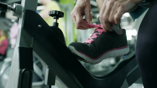 Senior woman tying shoelaces Senior woman tying shoelaces on her sneakers exercise bike stock videos & royalty-free footage