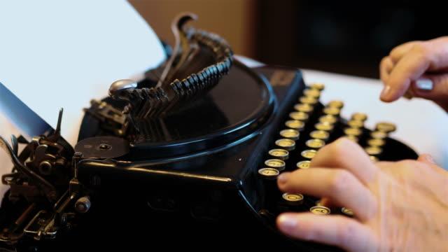 Senior woman typing on an old typewriter in 4k slow motion video