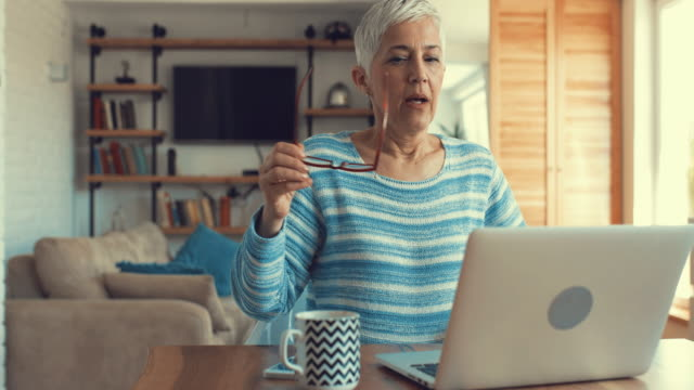 Senior woman typing on laptop while writing an e-mail at home. video