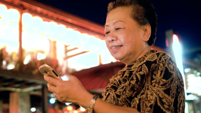 Senior woman uses a smartphone at night
