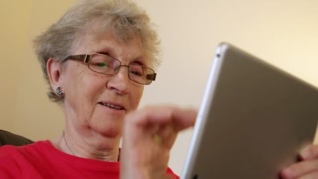 senior woman using a digital tablet. - mature women studio grey hair bildbanksvideor och videomaterial från bakom kulisserna
