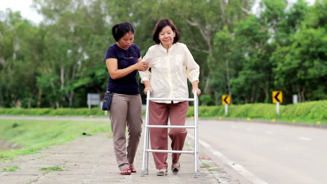 senior woman using a walker cross street video