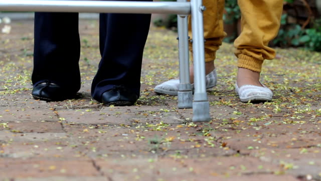 senior woman using a walker with caregiver in park. (dolly left) video