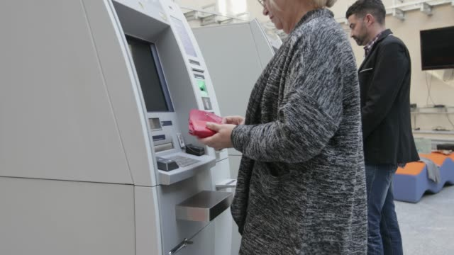 senior woman using atm, handheld shot - banks and atms stock videos & royalty-free footage