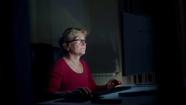 stockvideo's en b-roll-footage met senior vrouw met behulp van computer - overwerken