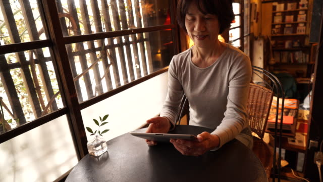 Senior woman using digital tablet in a cafe video