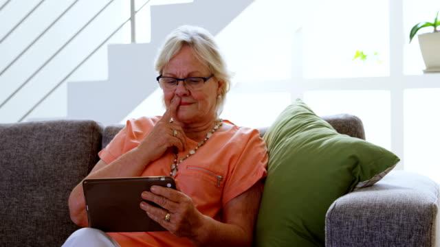 senior woman using digital tablet in living room 4k - 60 69 anni video stock e b–roll